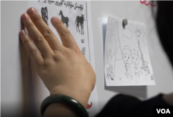 A teacher at Ana Care Education teaches Uyghur animal and color vocabulary.