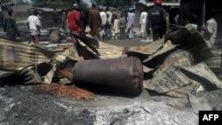 Les policiers assurent la sécurité devant les restes des maisons et des commerces incendiés dans le village de Konduga, dans le nord du Nigeria, 12 février 2014.
