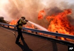 A firefighter battles a fire along the Ronald Reagan (118) Freeway in Simi Valley, California, Nov. 12, 2018.
