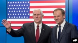United States Vice President Mike Pence, left, waves after shaking hands with EU Council President Donald Tusk as he arrives at the European Council building in Brussels, Belgium, on Feb. 20, 2017. (AP Photo/Thierry Monasse)
