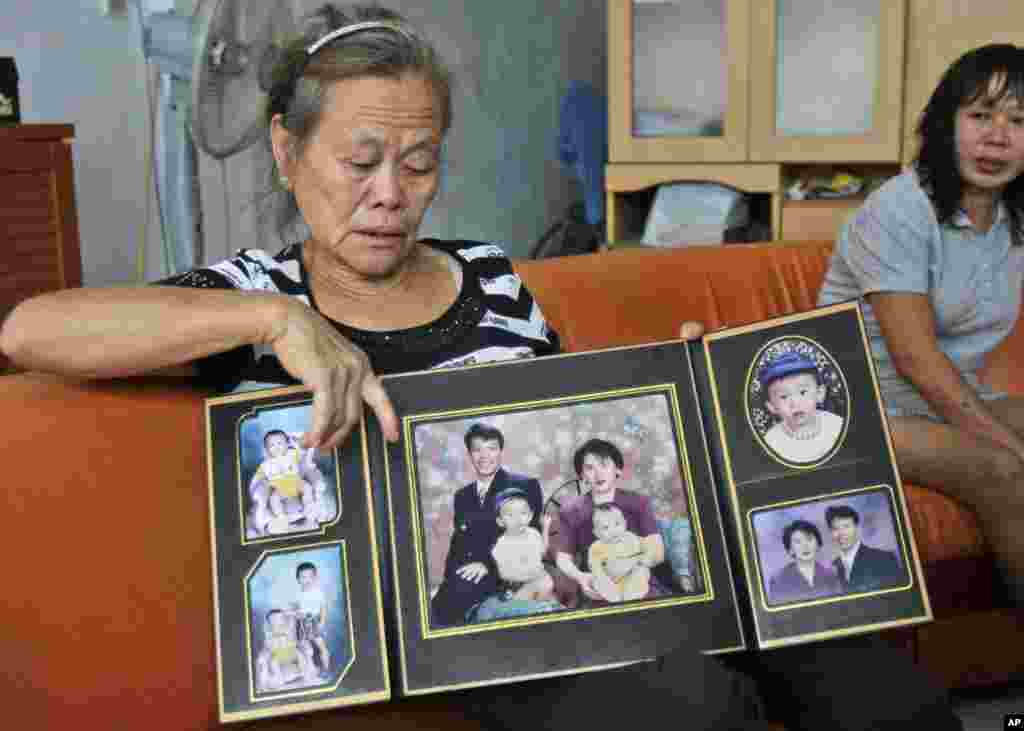 Suwarni, whose son was onboard flight MH370 with his wife, shows her son's family portraits at her residence in Medan, North Sumatra, Indonesia, March 25, 2014.
