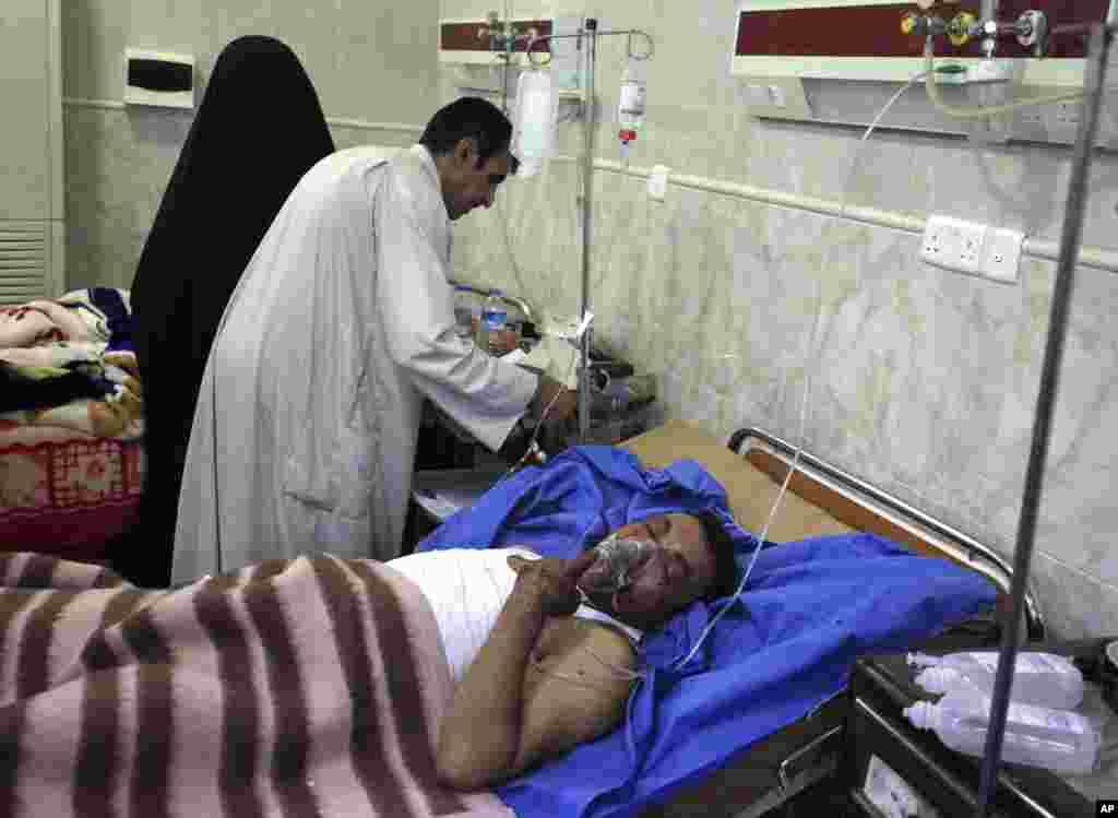 Küt şəhərində bomba hücumu zamanı yaralanan şəxsə yardım edilir - 16 iyun, 2013.