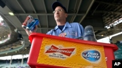 FILE - A beer vender holds up Budweiser and Bud Light at Wrigley Field in Chicago, Oct. 13, 2015.