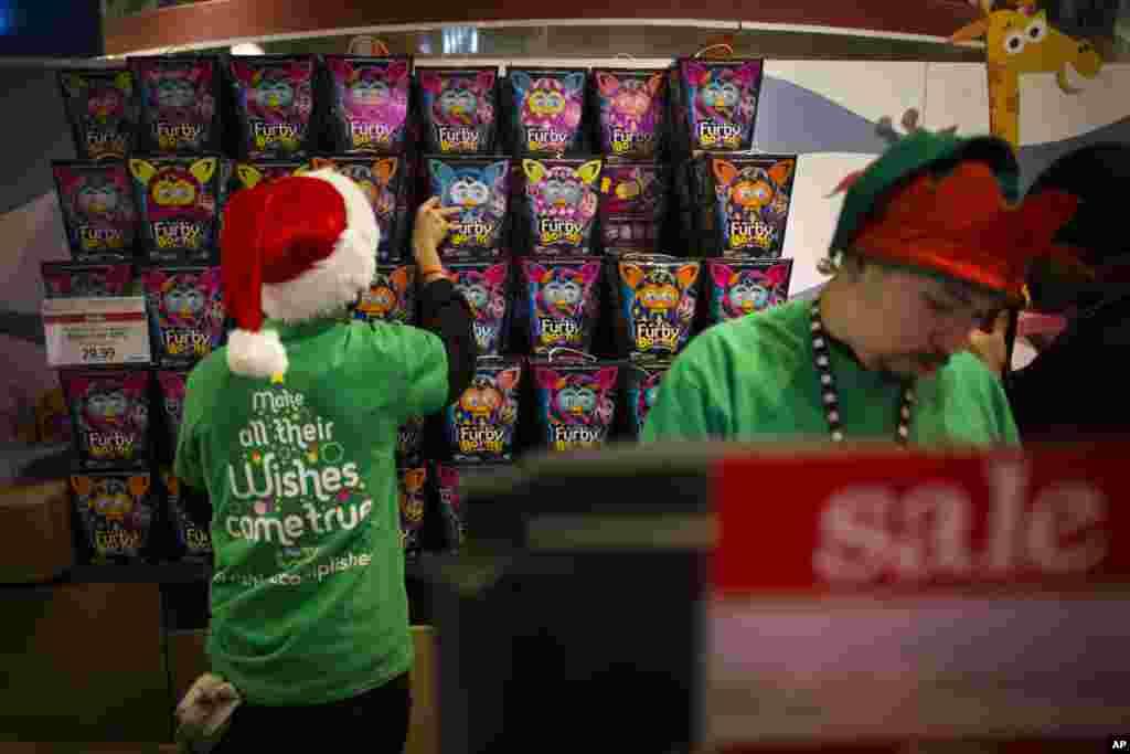 Para pegawai menyimpan persediaan boneka Furby di belakang kasir di toko Times Square Toys R' Us, New York (28/11).(AP/John Minchillo)