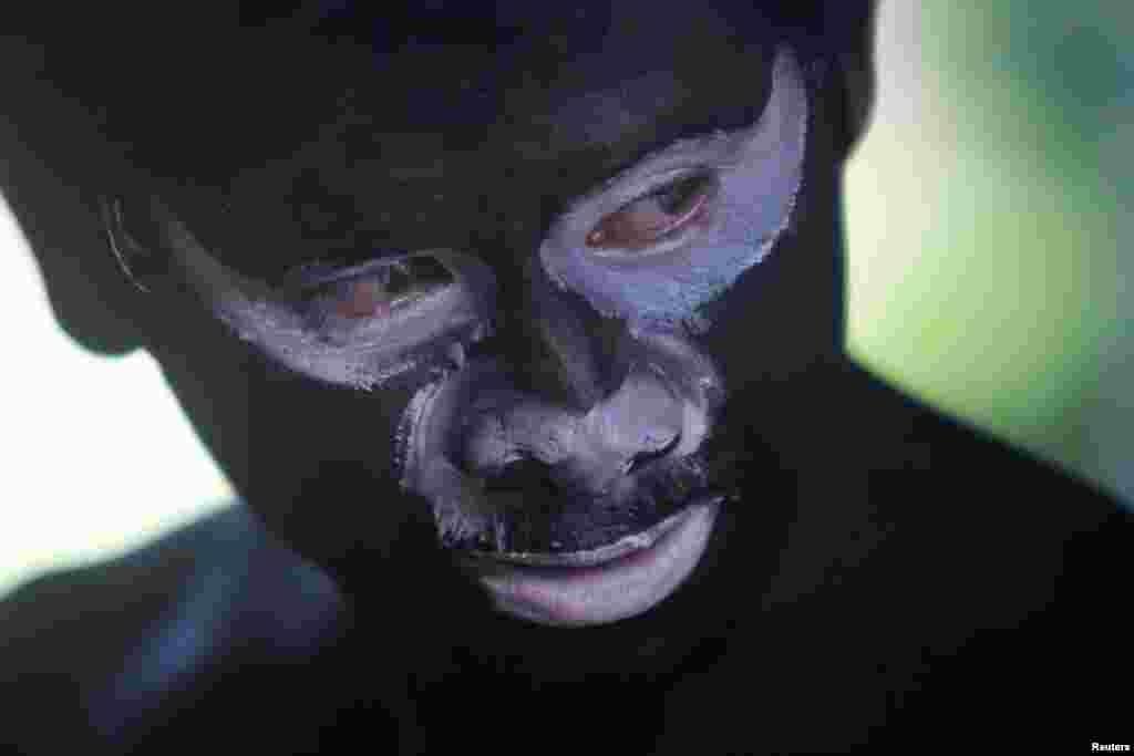 "Seorang pria mengecat wajah dan tubuhnya dengan cat hitam dalam festival keagamaan tradisional ""Lok Ta Pring Ka-Ek"" untuk meminta hujan di Phnom Penh, Kamboja."