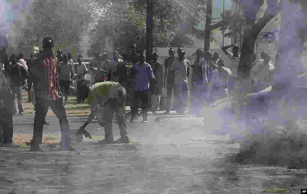 Des partisans du président Wade fuyant le gaz lacrymogène utilisé par la police pour les disperser à Dakar (AP)