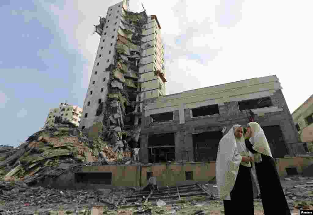 Palestinian women stand next to the remains of one of Gaza's tallest apartment towers, which was destroyed by an air strike, in Gaza City, Aug. 26, 2014.