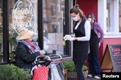 Seorang pegawai toko membantu pelanggan lansia pada hari pertama pembatasan jarak untuk mencegah virus corona di kawasan Mount Pleasant, Washington D.C, 2 April 2020. (Foto: Reuters)