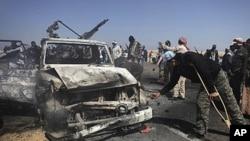 리비아 반군이 브레가 인근에 있는 도로에서 카다피군의 소유로 보이는 파괴된 차량을 살펴보고 있다.