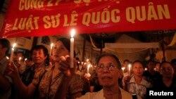 សកម្មជន Le Hien Duc ប្រឆាំងនឹងអំពើពុករលួយ (រូបខាងមុខ) និងអ្នកកាន់សាសនាកាតូលិកកាន់ភ្លើងទៀនក្នុងពេលសូត្រធម៌មួយសម្រាប់លោកមេធាវី Le Quoc Quan នៅព្រះវិហារ Thai Ha នៅក្នុងក្រុងហាណូយ កាលពីថ្ងៃទី៣០ ខែមិថុនា ឆ្នាំ២០១៣។