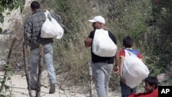 叙利亚难民背着土耳其村民捐献的食物跨过边界返回叙利亚