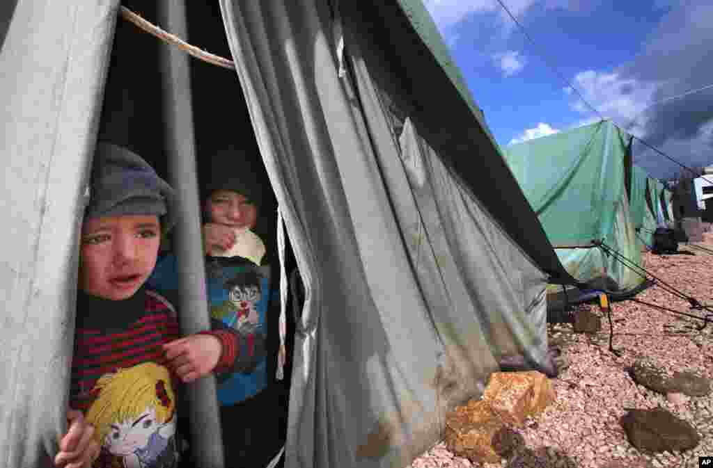 Syrian boys look outside their tent in Marj, Lebanon.