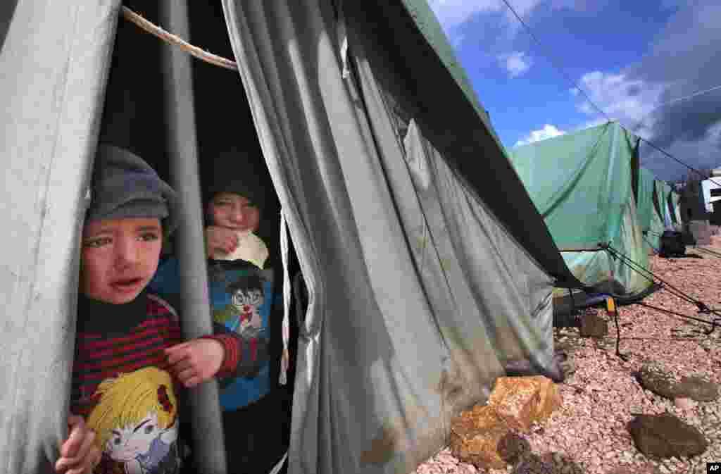 叙利亚男孩在黎巴嫩迈尔季地区他们所居住的帐篷里往外张望。