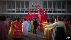 Seorang pria (tengah) memeriksa sekelompok penari saat menggelar tari rakyat di depan Stadion di Pyongyang, Korea Utara. Rakyat Korea Utara merayakan ulang tahun ke 101 kelahiran Kim Il Sung, pendiri negara Stalinis tersebut, Senin (15/4).