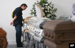 Roberto D'marchi gazes into the casket containing the remains of his cousin of Nilson Folle Jr., a victim of the Colombian air tragedy, in the parking garage of the San Vicente funeral home in Medellin, Colombia, Dec. 1, 2016. Because of the large number of casualties, the funeral home had to place the coffins in its parking garage. Forensic authorities say they have managed to identify a majority of the victims of Monday's crash and hope to finish their work Thursday. Folle Jr. was a member of the Chapecoense soccer club's board of directors.