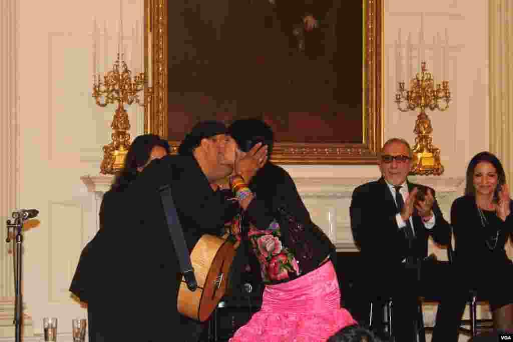 """Lila Downs saluda muy emocionada al guitarrista que la acompañó a entonar a todo pulmón el tradicional """"Cucurrucucu Paloma"""" en la Casa Blanca durante el taller conducido por el director del museo del Grammy, Robert Santelli."""