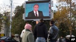 Građani prate obraćanje ruskog predsednika Vladimira Putina na ekranu na Trgu Nakimov u Sevastopolju, na Krimu