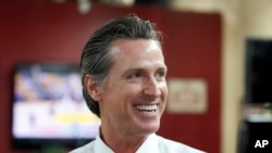 FILE - In this May 31, 2018 file photo Democratic Lt. Gov. Gavin Newsom smiles at a campaign stop at Stakely's Barber Salon in Los Angeles.