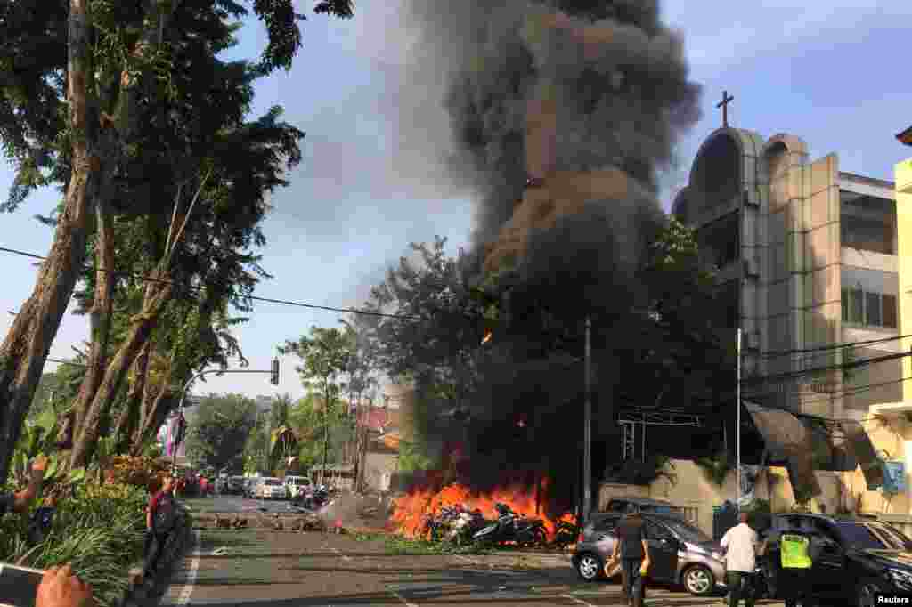 Motorcycles burn following a blast at the Pentecost Church Central Surabaya (GPPS), in Surabaya, East Java, Indonesia, in this photo provided by Antara Foto.