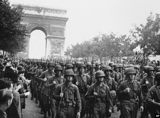FILE-In this photo provided by the U.S. Office of War Information, American troops march down the Champs Elysees, past the Arc de Triomphe, Sept. 12, 1944, as residents of Paris throng the sidewalks to cheer.