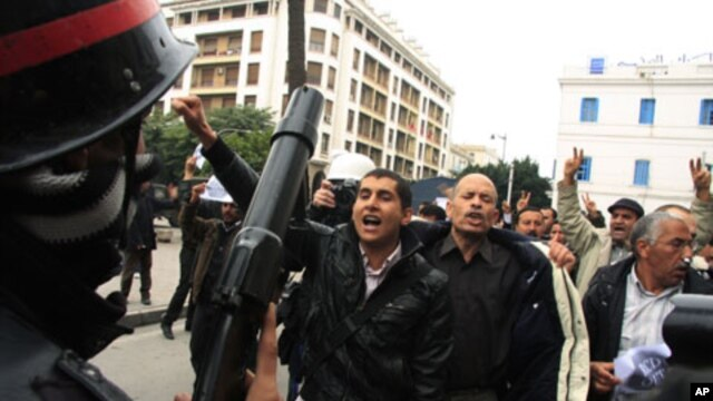 A riot policeman faces off with protesters during a demonstration in downtown Tunis, 18 Jan 2011