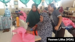 Produksi baju khusus untuk alat perlindungan diri di ruang jahit dan sablon di SMK Negeri 5 Palu, 31 Maret 2020. (Foto: VOA/Yoanes Litha)
