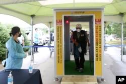 Seorang veteran Perang Korea berjalan melalui alat sterilisasi sebagai upaya pencegahan terhadap virus Covid-19 sebelum menghadiri upacara peringatan 70 tahun pecahnya Perang Korea di Cheorwon, dekat perbatasan dengan Korea Utara, Korea Selatan, 25 Juni 2020.