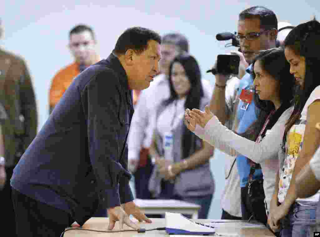 Chavez, left, speaks with an electoral worker at a polling station before casting his ballot for the presidential election in Caracas, October 7, 2012.