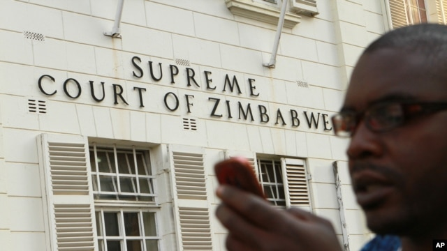 A journalist checks his mobile phone outside the Constitutional Court in Harare, Aug. 9, 2013.