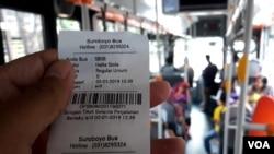 Tiket Suroboyo Bus diterima penumpang setelah menukar botol dan gelas plastik bekas kepada petugas di dalam bus (foto Petrus Riski/VOA).