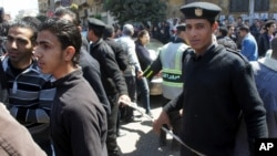 Security helps manage the tens of thousands who came to mourn the Coptic patriarch, Cairo, Egypt. March 18, 2012