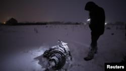 Un investigador junto a los restos de una turbina del avión Antonov AN-148 que se estrelló el domingo en las afueras de Moscú.