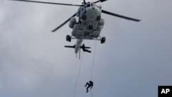 Des policiers sud-coréens descendent en rappel d'un hélicoptère lors d'un exercice antiterroriste dans le cadre de l'exercice Ulchi Freedom Guardian, à Goyang, en Corée du Sud, le 21 août 2017.