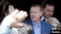 Turkey's Prime Minister Regep Tayyip Erdogan acknowledges supporters outside a polling station in Istanbul March 30, 2014.