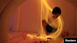 A boy relaxes with lights in a 'Snoezelen' room during yoga classes for children who typically have autism, brain injuries or developmental disabilities, in Lima, Peru, Jan. 27, 2012.