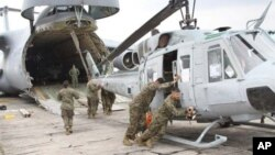 Marines unload a UH-1N Huey helicopter in Guatemala City, August 11, 2012