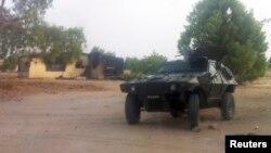Watamotar soja tana gadi a kifar wani gida da aka kona a garin Bama, Jihar Borno, ran 7 Mayu 2013