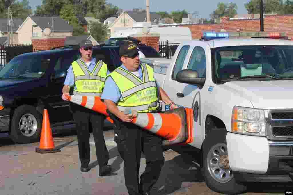 La policia local de St. Louis, Missouri, tratando de establecer ciertos límites o barricadas en los alrededores de la iglesia. [Foto: Alberto Pimienta, VOA]