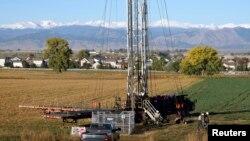 Dengan pegunungan Rocky di latar belakang, para pekerja mengebor sumur minyak di Longmont, Colorado,14/10/ 2014.