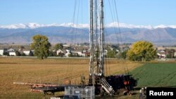FILE - Workers drill an oil well within sight of houses against a Rocky Mountain backdrop near Longmont, Colorado, Oct. 14, 2014.