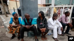 Staff members of This Day newspaper sit outside, as workers barricaded the front office due to non payment of salaries in Lagos, May 10, 2013.