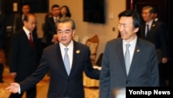 왕이 중국 외교부장(왼쪽)과 윤병세 한국 외교장관이 25일 라오스 비엔티안에서 양자회담 장소로 입장하고 있다.