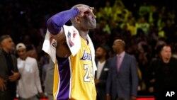 Pemain Los Angeles Lakers, Kobe Bryant, memberi hormat kepada para penggemar dalam pertandingan NBA terakhirnya melawan Utah Jazz (13/4). (AP/Jae C. Hong)