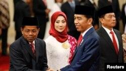 President Joko Widodo (kanan) berjabat tangan dengan Menteri Sosial baru, Idrus Marham (kiri), didampingi istri, Ridho Ekasari (tengah), seusai pelantikan di Istana Presiden, Jakarta, 17 Januari 2018.