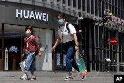 រូបឯកសារ៖ មនុស្សម្នាពាក់ម៉ាសដើរកាត់ហាងរបស់ក្រុមហ៊ុន Huawei មួយនៅក្នុងក្រុងប៉េកាំង កាលពីថ្ងៃទី១៨ ខែឧសភា ឆ្នាំ២០២០។