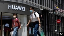 "Residents wearing face masks to protect against the coronavirus walk past a Huawei retail store in Beijing on Monday, May 18, 2020. China's commerce ministry says it will take ""all necessary measures"" in response to new U.S. restrictions on Chinese…"