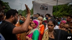 A man tries to calm protesters down as they demonstrate outside a crematorium where a 9-year-old girl was, according to her parents and protesters, raped and killed in New Delhi, India, Aug. 5, 2021.