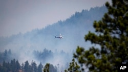 A helicopter pilot prepares to drop water on a wildfire burning in Lytton, British Columbia, July 2, 2021. Officials on Friday hunted for any missing residents of the town, which was destroyed by wildfire.