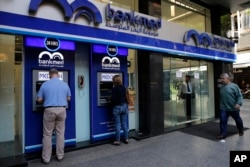 FILE - People use an ATM outside a bank, in Beirut, Lebanon, Nov. 20, 2019.