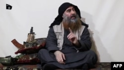 FILE - The chief of the Islamic State group, Abu Bakr al-Baghdadi, purportedly appears for the first time in five years in a propaganda video in an undisclosed location, in this undated TV grab taken from video released April 29 by Al-Furqan media.